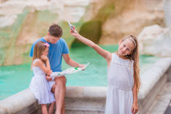 Family on Fontana di Trevi, Rome, Italy. Happy father and kids enjoy italian vacation holiday in Europe. Happy family near Fontana di Trevi with city map Royalty Free Stock Photography