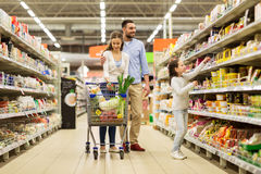 Family with food in shopping cart at grocery store. Sale, consumerism and people concept - happy family with child and shopping cart buying food at grocery store Royalty Free Stock Photos