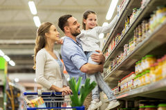 Family with food in shopping cart at grocery store Stock Photos