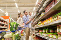 Family with food in shopping cart at grocery store. Sale, consumerism and people concept - happy family with child and shopping cart buying food at grocery store royalty free stock image