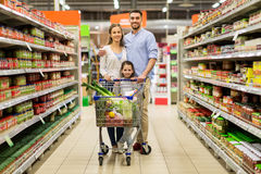 Family with food in shopping cart at grocery store. Sale, consumerism and people concept - happy family with child and shopping cart buying food at grocery store stock images