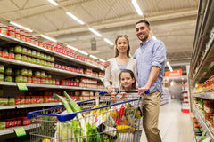 Family with food in shopping cart at grocery store. Sale, consumerism and people concept - happy family with child and shopping cart buying food at grocery store stock photography