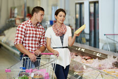Family at food shopping in supermarket. Young Family couple choosing bio food chicken meat in grocery supermarket during weekly shopping Royalty Free Stock Image