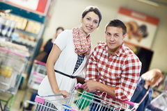 Family at food shopping in supermarket. Young Family couple with trolley cart in meat grocery supermarket during weekly food shopping Stock Photography