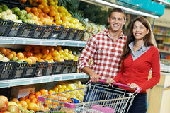 Family at food shopping in supermarket. Young Family couple choosing bio food fruit in vegetable supermarket during weekly shopping Stock Images