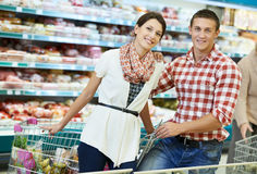 Family at food shopping in supermarket. Young Family couple choosing bio food in grocery supermarket during weekly shopping Royalty Free Stock Image