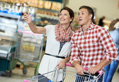 Family at food shopping in supermarket. Family couple with trolley cart in meat grocery supermarket during weekly food shopping Stock Photography
