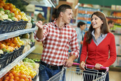 Family at food shopping in supermarket. Young Family couple choosing bio food fruit in vegetable supermarket during weekly shopping Stock Photo