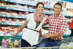 Family at food shopping in supermarket. Young Family couple choosing bio food in grocery supermarket during weekly shopping Stock Photography