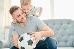 Family of Football Lovers. Happy young father and his cute little son having fun together while taking break from playing football, interior of cozy living room stock photos