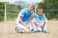 Family football players. Portrait of father with son in soccer uniform during break on football pitch Royalty Free Stock Image