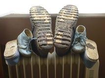 Family footwear heated on heater. Family footwear heated on oil heater Stock Photos
