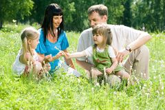 Family in forest. Portrait of happy family sitting on the lawn in the forest stock image