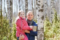 Family in the forest collecting birch sap Stock Photography