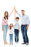 Family forming shape of home. Young family with two children on white background royalty free stock photo