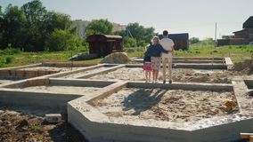 The family is on the foundation of their future home. New beginnings concept.  stock video footage