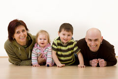 Family of four. Portrait of a mother and father and two children lying on the floor royalty free stock images