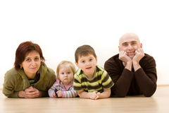 Family of four. Portrait of a mother and father and two children lying on the floor stock image