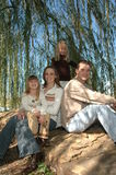 Family of Four. An american family take their portraits in nature sitting outside on a big rock under a weeping willow tree Stock Photo