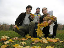 Family of four with autumn leaves. Parents with child and baby royalty free stock photography