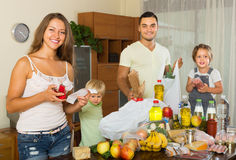 Family of four with bags of food. Happy middle-class family of four with bags of food at home royalty free stock photos