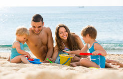 Family of four at the beach Royalty Free Stock Photo