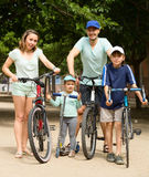 Family of four with bicycles and scooter in vacation. At park Stock Images