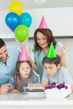 Family of four blowing cake. At a birthday party royalty free stock photos