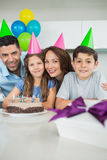 Family of four with cake and gifts at birthday party. Portrait of a family of four with cake and gifts at a birthday party stock image