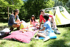 Family of four camping in tent. Family doing camping in the forest stock photography