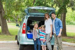 Family of four by car trunk while on picnic Royalty Free Stock Image