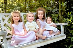 Family of Four Children. Four children sit on a garden swing.  Three girls are dressed in light pink dresses.  The one boy is dressed in a yellow jumper with Stock Photography