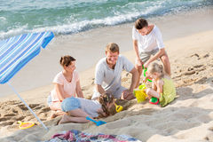 Family with four children playing on beach Royalty Free Stock Photography