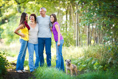 Family of four with a cute dog outdoors Stock Photos
