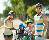 Family of four cycling on street Royalty Free Stock Images