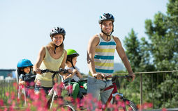 Family of four cycling on street Royalty Free Stock Photo