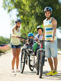 Family of four cycling on street Stock Photo