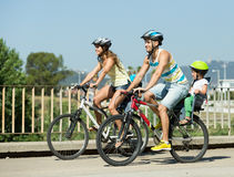 Family of four cycling on street Stock Photos