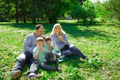 A family of four eat ice cream outdoors. Stock Photography