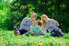 A family of four eat ice cream outdoors. Stock Images