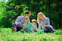 A family of four eat ice cream outdoors. Royalty Free Stock Photography