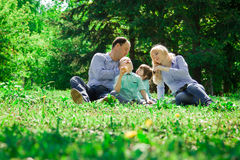 A family of four eat ice cream outdoors. Royalty Free Stock Photo