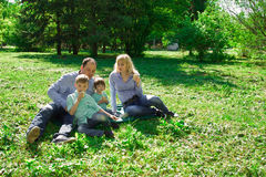 A family of four eat ice cream outdoors. Royalty Free Stock Image