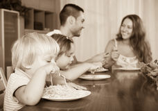 Family of four eating spaghetti. Positive smiling young family of four having lunch with spaghetti at home Royalty Free Stock Photography