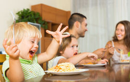 Family of four eating spaghetti. Smiling young family of four having lunch with spaghetti at home. Focus on girl Stock Photo