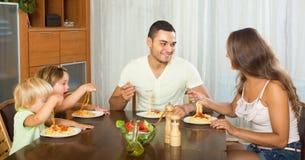 Family of four eating spaghetti Stock Photos