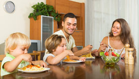 Family of four eating spaghetti. Young smiling family of four eating spaghetti at home interior. Focus on man Royalty Free Stock Images