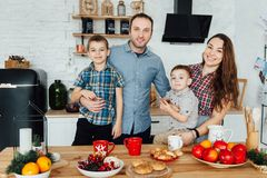 Family of four embracing sitting on the kitchen. Two sons hug their parents stock photography