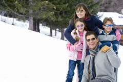 Family of four embracing in snow field, wearing sunglasses, smiling, portrait Royalty Free Stock Images