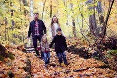 Family of four enjoying golden leaves in autumn park Stock Photos
